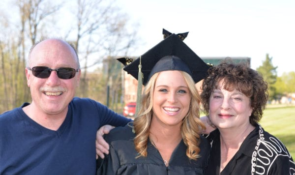 Happy female grad with her mom and dad