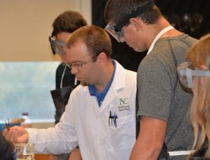 Photo of students in bioscience lab work with instructor.